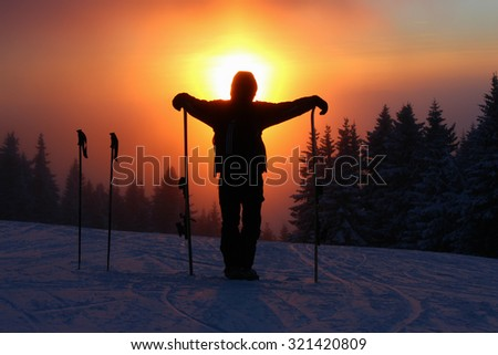 Silhouette of young man skying in mountains on beautiful sunset - stock photo