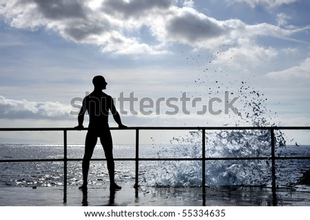 Silhouette of young man standing at the seaside -wave splash - stock photo