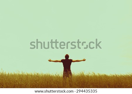Silhouette of young man standing with hands open wide - stock photo