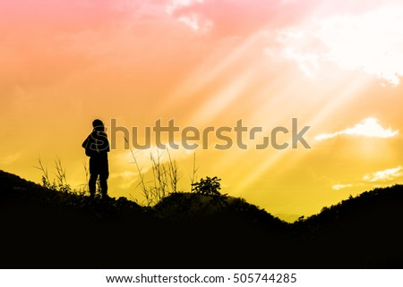 Silhouette of Young Man Traveler with backpack relaxing outdoor, Lifestyle hiking concept with sunrise,