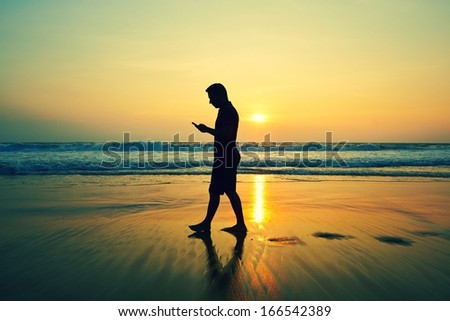 Silhouette of young man with mobile phone on the beach at sunset  - stock photo