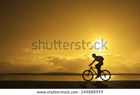 silhouette of young man woman cyclist on sunset sky with clouds Sun on water texture with ripples ride along seashore summer beach at yellow evening horizon sea yellow sunset heaven background Outdoor - stock photo