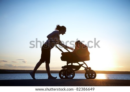 Silhouette of  young mother enjoying motherhood - stock photo
