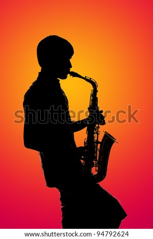 Silhouette of young musician with Saxophone - stock photo
