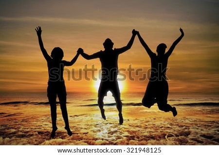 Silhouette of Young people jumping in sunset on the beach