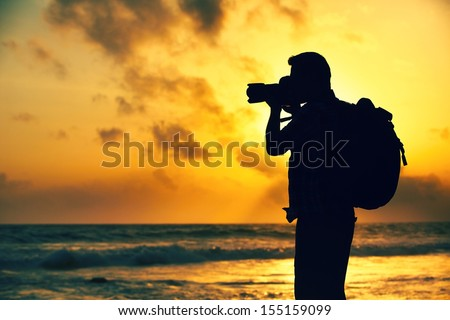 Silhouette of young photographer on the beach - stock photo