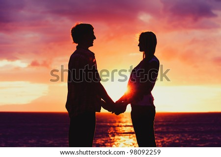 Silhouette of Young Romantic Couple at Sunset - stock photo