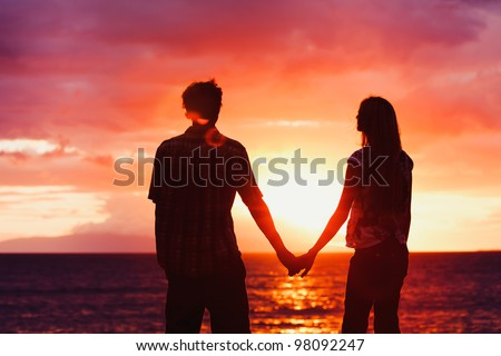 Silhouette of Young Romantic Couple Holding Hands at Sunset