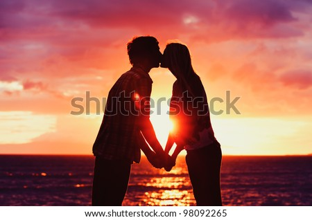 Silhouette of Young Romantic Couple Kissing at Sunset - stock photo