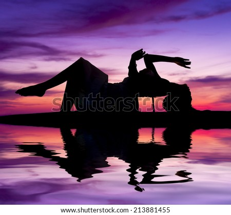 Silhouette of young sensuality beautiful woman during sunset - stock photo