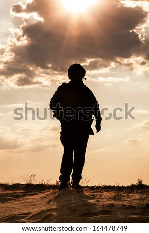 Silhouette of young soldier in military helmet against the sun - stock photo