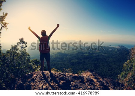 silhouette of young successful woman hiker open arms on mountain peak - stock photo