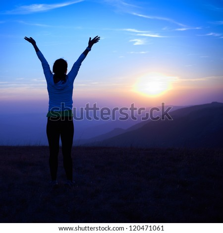 Silhouette of young woman against sunset with blue sky