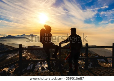 Silhouette of young woman and man with backpacks and sticks on mountains at sunset.