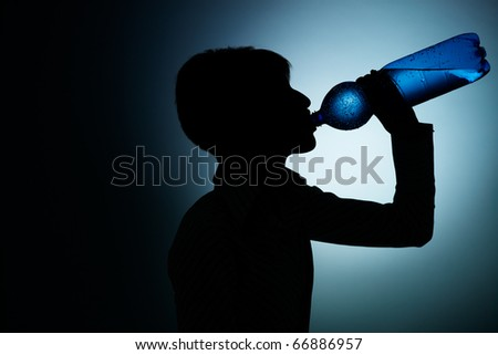 silhouette of young woman drinking water from bottle on blue background. Horizontal shape, side view, copy space