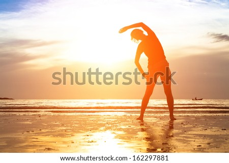 Silhouette of young woman, exercise on the beach at sunset. - stock photo