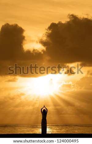 Silhouette of young woman is doing yoga at sunrise - stock photo