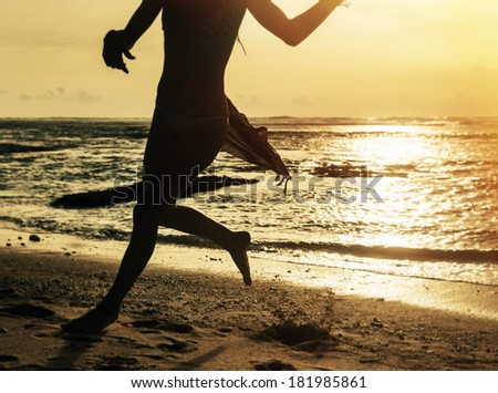 Silhouette of young woman jogging along the ocean shore at sunset - stock photo