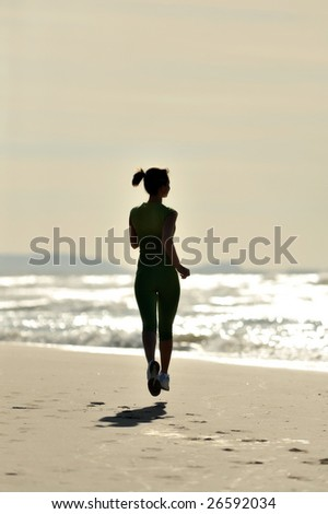 silhouette of young woman jogging on the beach at sunrise - stock photo