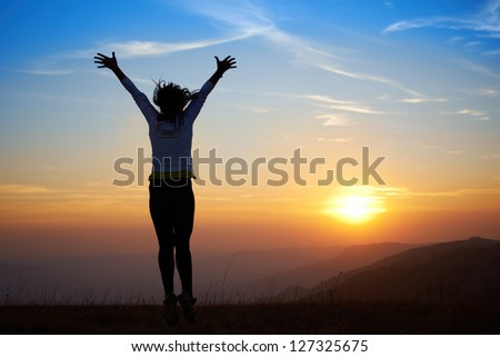 Silhouette of young woman jumping against sunset - stock photo