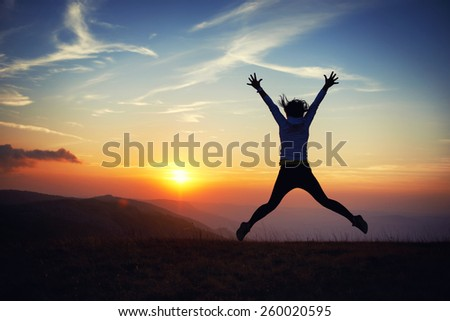 Silhouette of young woman jumping against sunset with blue sky. - stock photo