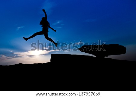 Silhouette of young woman jumping over the rock on blue sky background - stock photo