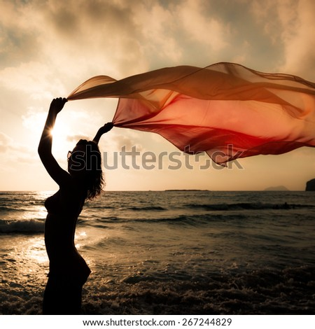 Silhouette of young woman jumping with silk fabric at the beach. Summer vacation concept - stock photo