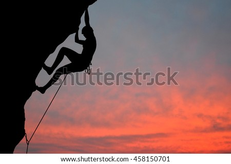 Silhouette of young woman lead climbing on overhanging cliff, sun, beautiful colorful sky and clouds behind. Climber on top rope, hanging on rock during sunset.