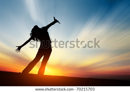 Silhouette of young woman on sunset - stock photo