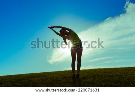 Silhouette of young woman practicing yoga  - stock photo