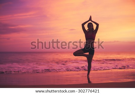 Silhouette of young woman practicing yoga on the beach at sunset. Healthy Active Lifestyle.
