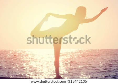 Silhouette of young woman practicing yoga on the beach near the sea, ocean at sunset