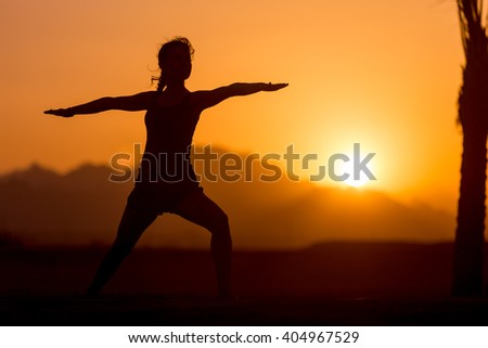 Silhouette of young woman practicing yoga or pilates at sunset or sunrise in beautiful mountain location, doing lunge exercise, standing in Warrior II pose, Virabhadrasana 2 - stock photo