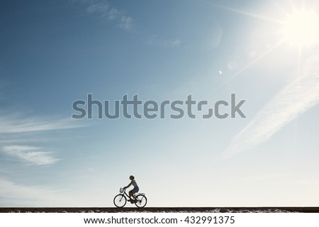Silhouette of young woman riding old bicycle with basket against blue sky during summer vacation - healthy travel lifestyle concept - stock photo