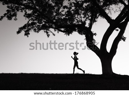Silhouette of young woman running. - stock photo