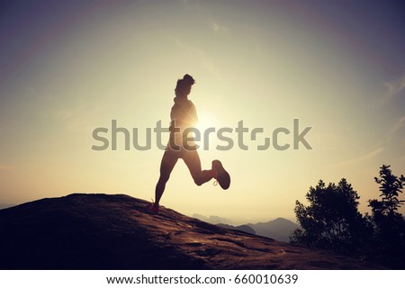 silhouette of young woman running on mountain top