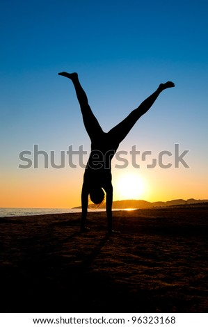 Silhouette of Young Woman Turning Cartwheel On Beach - stock photo