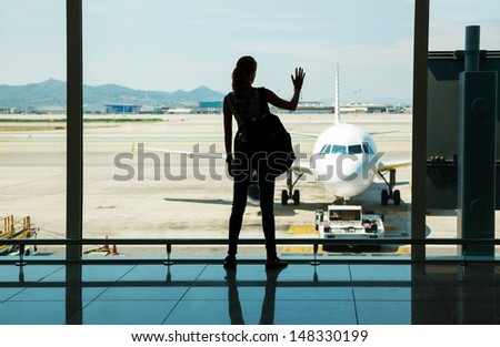 Silhouette of young woman waiting for the flight - stock photo