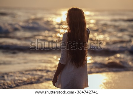 Silhouette of Young Woman Watching Sea Sunset - stock photo