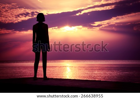 Silhouette of Young Woman Watching Sea Sunset. Breathtaking Nature Background. Toned Photo with Copy Space. - stock photo
