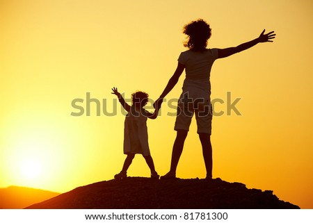 Silhouette of young woman with child against the bright sunset