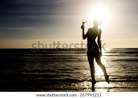 silhouette of young woman with glass of tropical cocktail on sunset sea background - stock photo