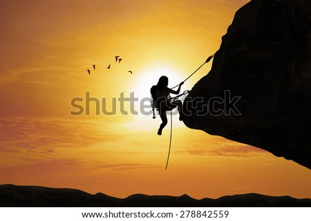 Silhouette of young women try to climb the mountain at sunset time - stock photo