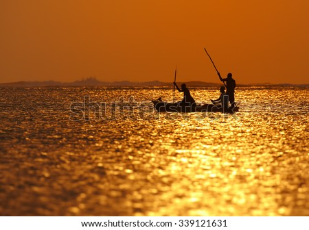 Silhouette of Zanzibar fishermen returning from fishing in the setting sun reflecting on the surface of the sea - stock photo