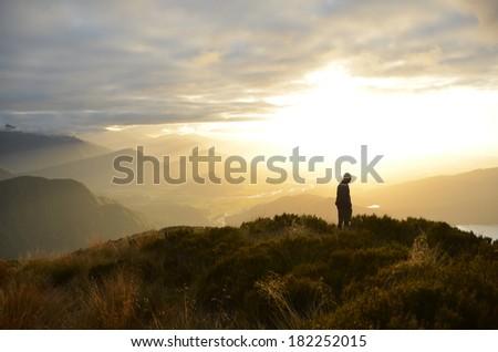Silhouette on Mountain Peak - stock photo