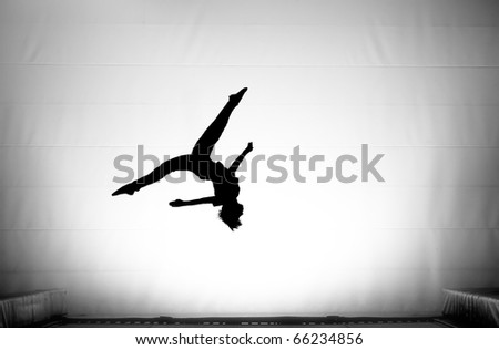 silhouette on trampoline doing a somersault with the splits - stock photo