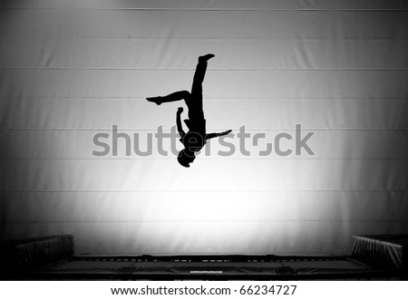 silhouette on trampoline doing somersault - stock photo
