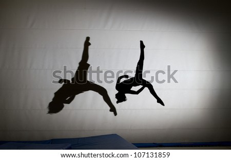 silhouette on trampoline with shadow - stock photo