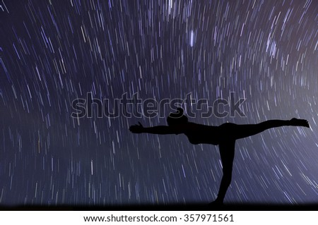 silhouette one woman with professional yoga posture over startrail background.
