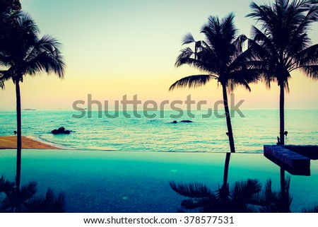 Silhouette palm tree and Beautiful luxury hotel swimming pool at twilight times - Vintage Filter - stock photo